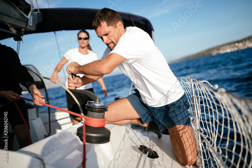 Fototapeta Handsome strong man sailing with his friends