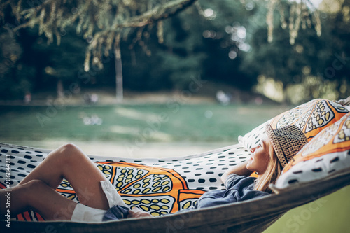 stylish hipster woman relaxing in hammock in sunny summer park. travel and wanderlust concept. blonde girl resting in forest, smiling and enjoying day. summer vacation, space for text