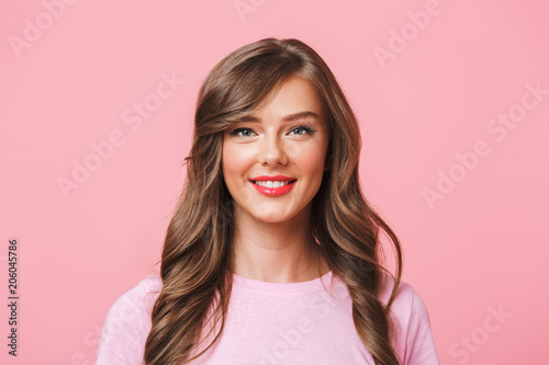 Image closeup of young european woman 20s with long curly hairstyle and evening makeup smiling at camera with happy look, isolated over pink background