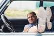 man with glasses resting in the car