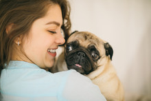 Young Woman Smiling Looking To Small Pug Dog. Family Love