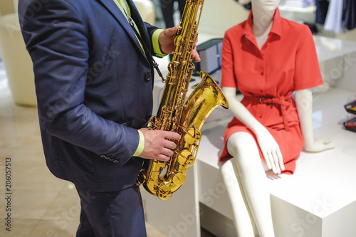 Photo  musician plays the saxophone performance at a concert in shopping center of wome