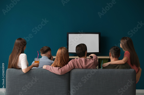 Young people watching TV at home