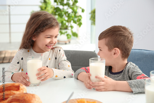 Cute little kids having breakfast with milk at table