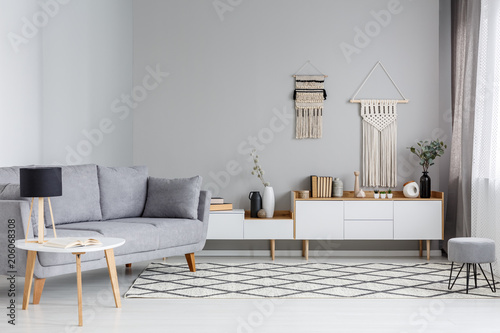Foto op Canvas Restaurant Lamp on table next to grey sofa in scandi living room interior with DIY decor above cupboard. Real photo