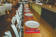 canvas print picture Close-up view of the row of the chairs and table with the white plates and the flatware on the red serviettes. Contemporary interior of the restaurant. Modern decoration in bright colors.