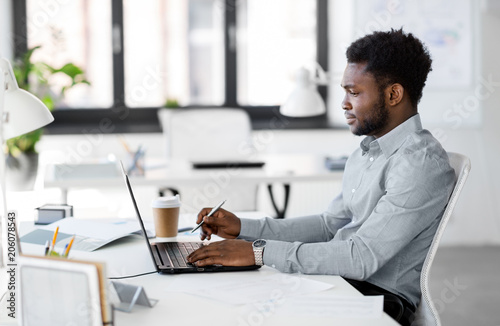 business, people and technology concept - african american businessman with laptop computer working at office