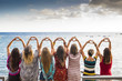 canvas print picture - seven girls from the backside doing a heart with the hands looking at the ocean waiting the sunset in vacation leisure activity. friendshipt all together forever concept, travel to sea places