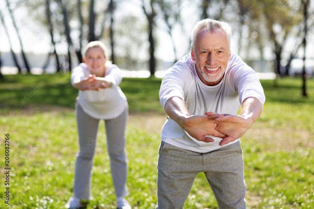 Fototapeta Useful exercise. Cheerful aged man leaning forward while doing exercises