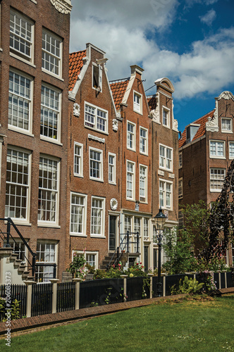 Photo  Semidetached typical houses and green garden at Begijnhof, a medieval semi-monastic community in Amsterdam