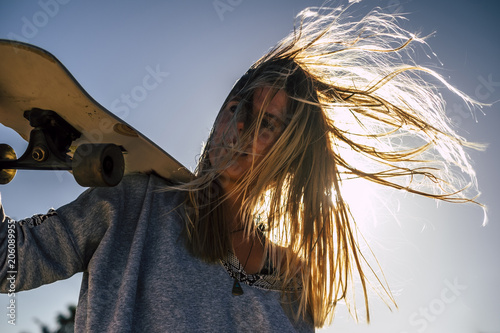 Leinwand Poster long blonde hair moved by the wind in a summer day of vacation for beautiful blonde model with skateboard