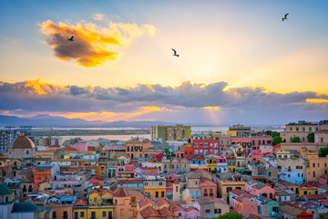 Panel Szklany Kolorowe domki Sunset on Cagliari, panorama of the old city center with traditional colored houses with beautiful yellow-pink clouds and seagull's in the sky, Sardinia Island, Italy