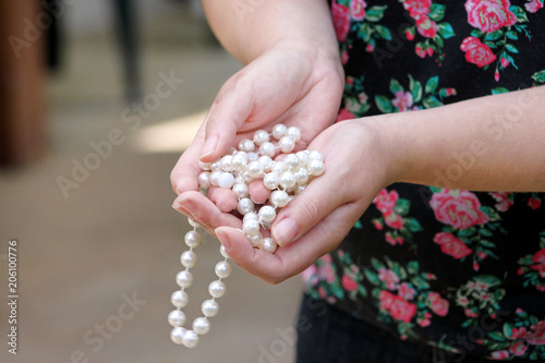 Women hands holding pearl beads jewelery. Closeup of female hand with pearl jewelry. Female hand holding a string of pearl. White pearl necklace. Fashion and beauty.
