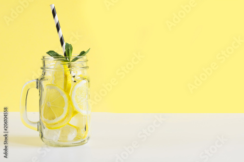 Valokuva Fresh summer fruits water or lemonade with lemon and mint on yellow background