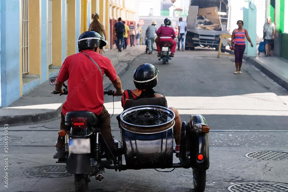 Fototapeta Santiago de Cuba, CUBA Couple riding in motorcycle with sidecar on the road ni Santiago de Cuba.