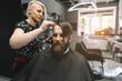 Stylish hairdresser cutting hair of client at barber shop. Beard man getting haircut at salon.