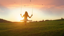 SILHOUETTE: Unrecognizable Young Woman Swaying On Swing At Golden Summer Sunset