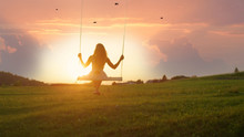 SILHOUETTE: Unrecognizable Young Woman Swaying On Swing At Golden Summer Sunrise