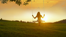 SILHOUETTE: Unrecognizable Girl Swinging On A Tree Swing At Golden Summer Sunset