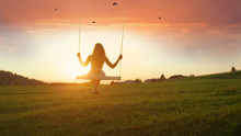 SILHOUETTE: Unknown Girl Swaying On Wooden Swing At Golden Sunset In Spring