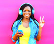canvas print picture - Cool african girl in headphones listens to music over pink background