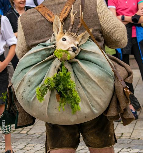 Jäger trägt ein erlegtes Reh in einem Beutel