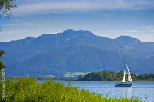 Segelboot auf dem Chiemsee in Bayern mit Berg Kampenwand