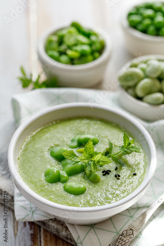Vegetable creamy soup. Broad bean soup sprinkled with  fresh mint and nigella. Delicious and nutritious vegetarian food. Healthy eating concept.