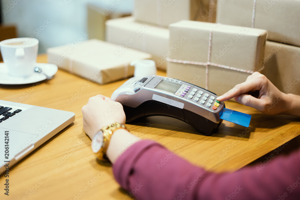 Fototapeta female employee taking payment from customer,woman hand with credit card swipe through terminal paying by credit-card at the shopping center. Focus on hands entering security pin in credit card reader
