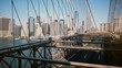 Timelapse panoramic shot of New York seen through Brooklyn Bridge cables. Downtown buildings background on sunny day 4K.