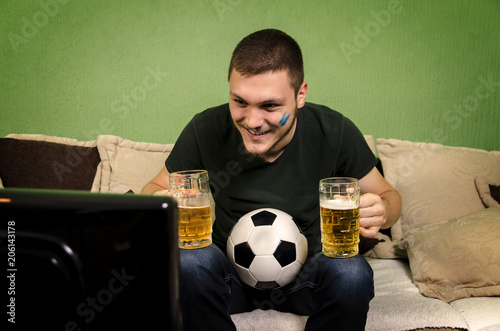 Fotografie, Obraz  Young adult guy sitting with two beer mugs and soccer ball, watching match on TV