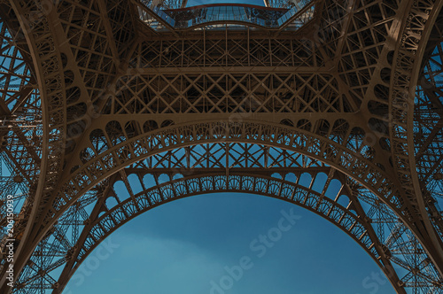 Fotografia Bottom view of Eiffel Tower made in iron and Art Nouveau style, with sunny blue sky in Paris