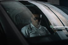 Male Undercover Agent In Sunglasses Sitting In Car With Paper Cup Of Coffee While Doing Surveillance