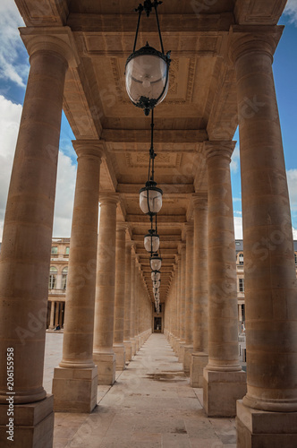 Pathway with marble colonnade between courtyards and cloudy sky at the Palais-Royal in Paris Fototapete
