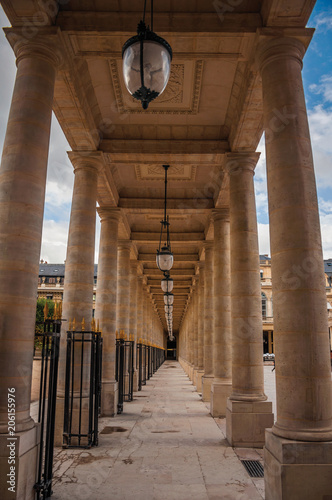 Fotografie, Obraz  Pathway with marble colonnade between courtyards and cloudy sky at the Palais-Royal in Paris