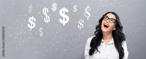 Fototapeta Dollars with happy young businesswoman on a gray background obraz