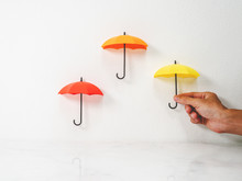 Mini Umbrella Decor With Man Hand Holding Color Red, Orange And Yellow.