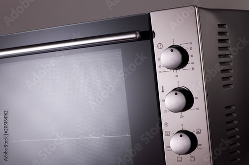 thermostat and handles on a modern microwave. kitchen equipment