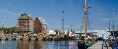 Staande foto Poort SEA PORT - Old grain warehouses and a sailboat at the wharf