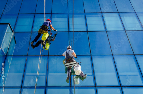 Photo Industrial climbers are applying silicone on joints between windows