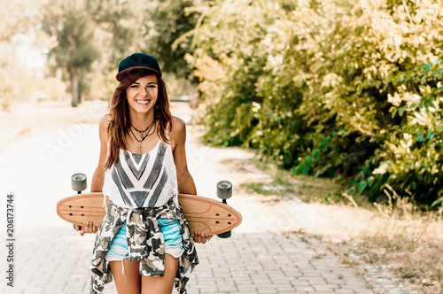 Portrait of beautiful brunette girl hold her wooden longboard skateboard