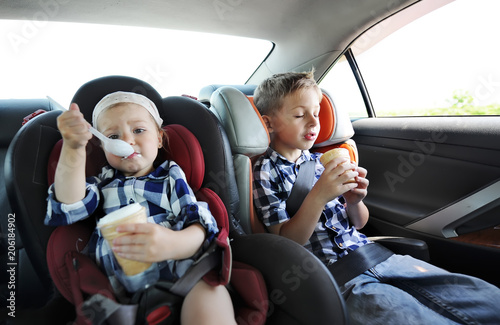 Valokuva  Little sister and her brother in safety car seat eating sweet ice cream