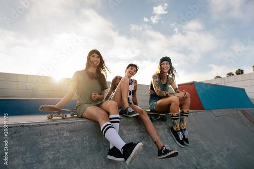 Group of women sitting on ramp in skate park