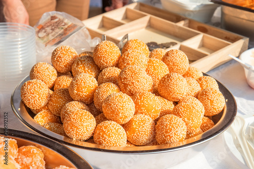a bunch of sesame balls served on a metal bowl on a farm street market