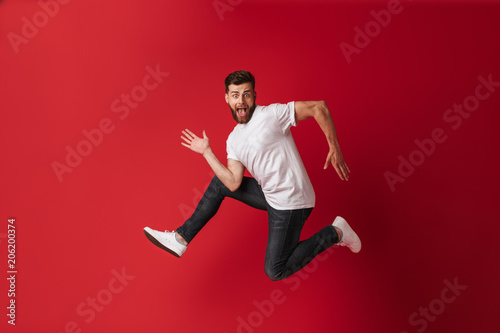 Handsome excited young man running Wallpaper Mural