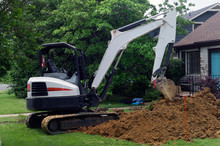 Major Homeowner Problem: Excavator Digging Out Lawn To Access Water Main Problem Leading To House.