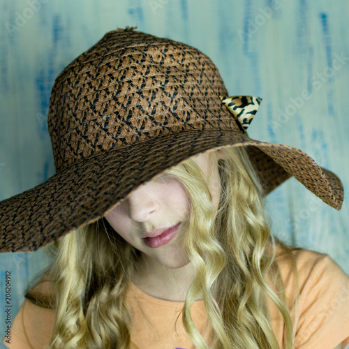 33021db82d4 A teenage girl in a big hat covering her face against a wooden background.