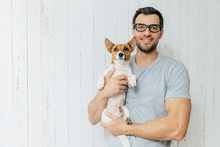 Attractive Cheerful Caucasian Male In Casual T Shirt, Spectacles, Holds Favourite Pet, Stands Against White Wooden Background With Blank Space. Happy Unshaven Man With His Jack Russell Terrier
