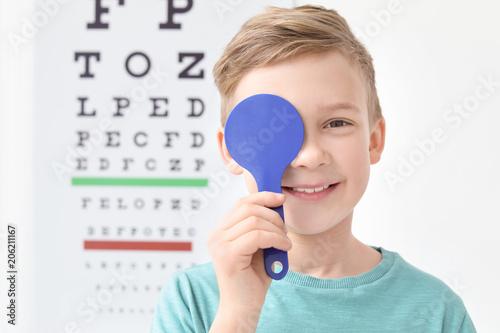 Cuadros en Lienzo Cute little boy near eye chart in ophthalmologist office