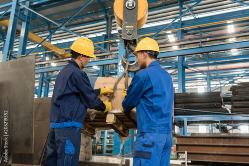 Fotografia Two Asian workers handling heavy loading lifted by crane in the interior of a me